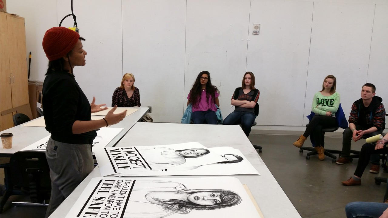 Soraya Chemally talking to students about the posters to be wheatpasted