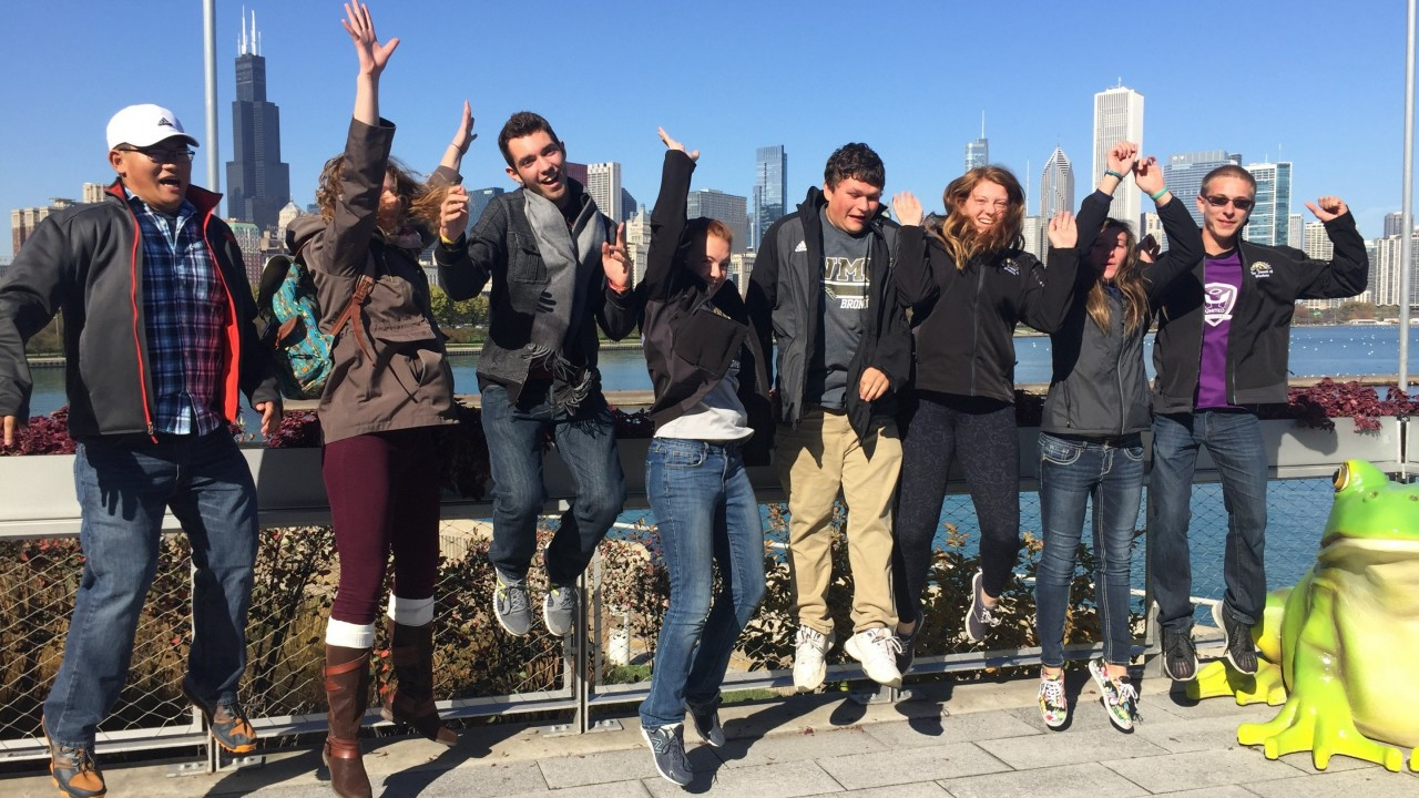 Honors college students jumping next to a sculpture of a giant frog in Chicago.