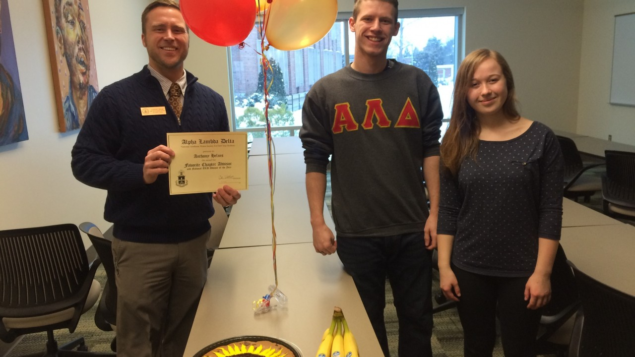 Two Alpha Lambda Delta students with balloons giving an award, a cake, and bananas to advisor Anthony Helms.