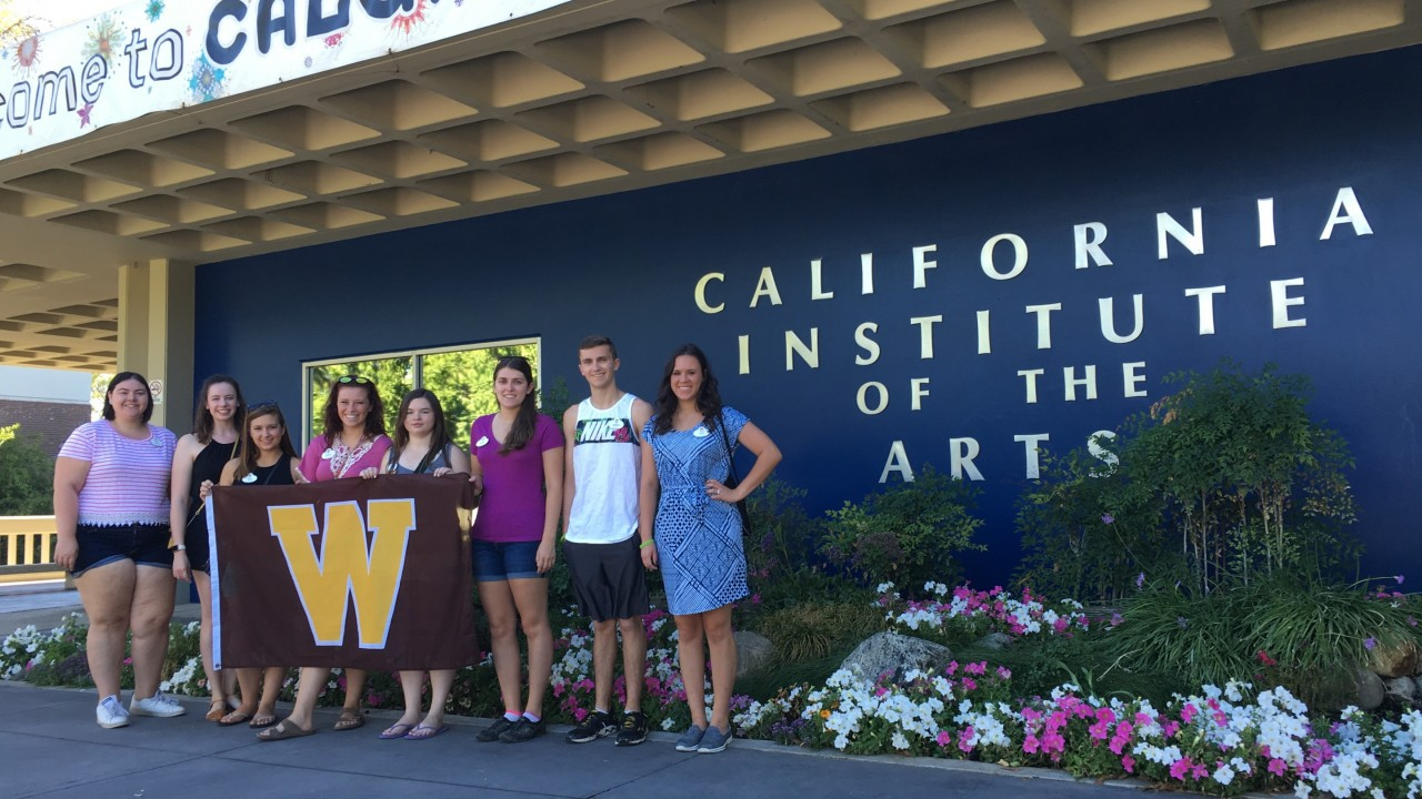 Honors college students holding a W flag standing in front of the California Institute of the Arts.