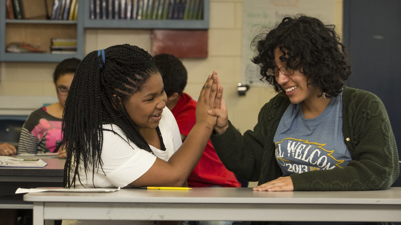 Young woman and middle school student high fiving each other while seated at a table.