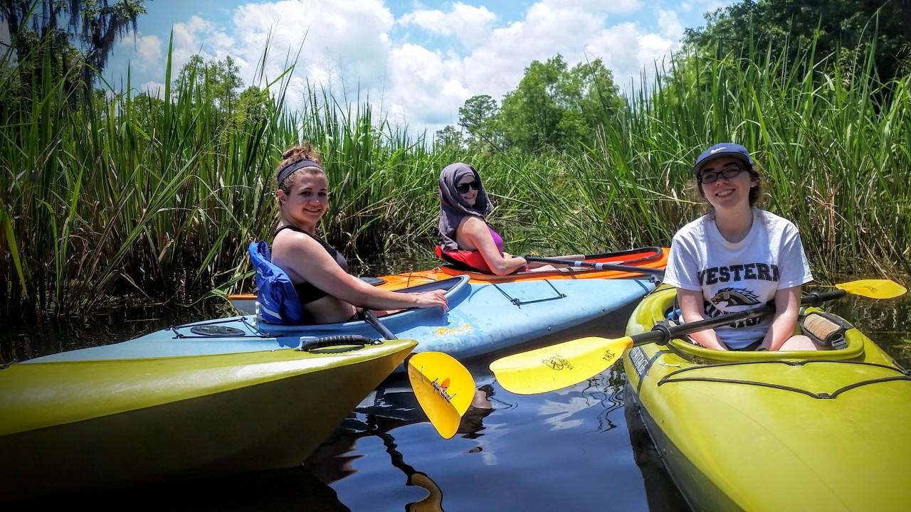 Three students kayaking in Louisiana.