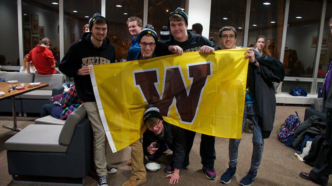 Small group of male honors students holding a W flag at an ice cream social in a residence hall.
