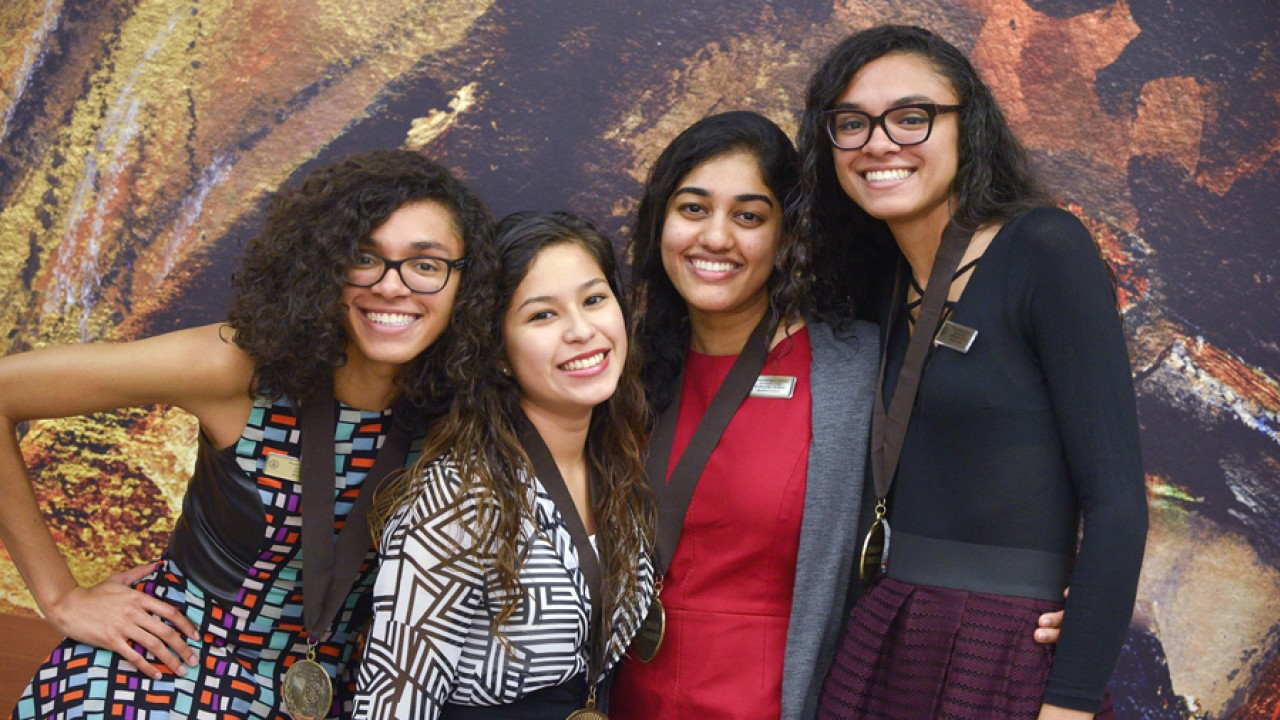 Four young women standing in front of a painting wearing their 2014 Medallions.