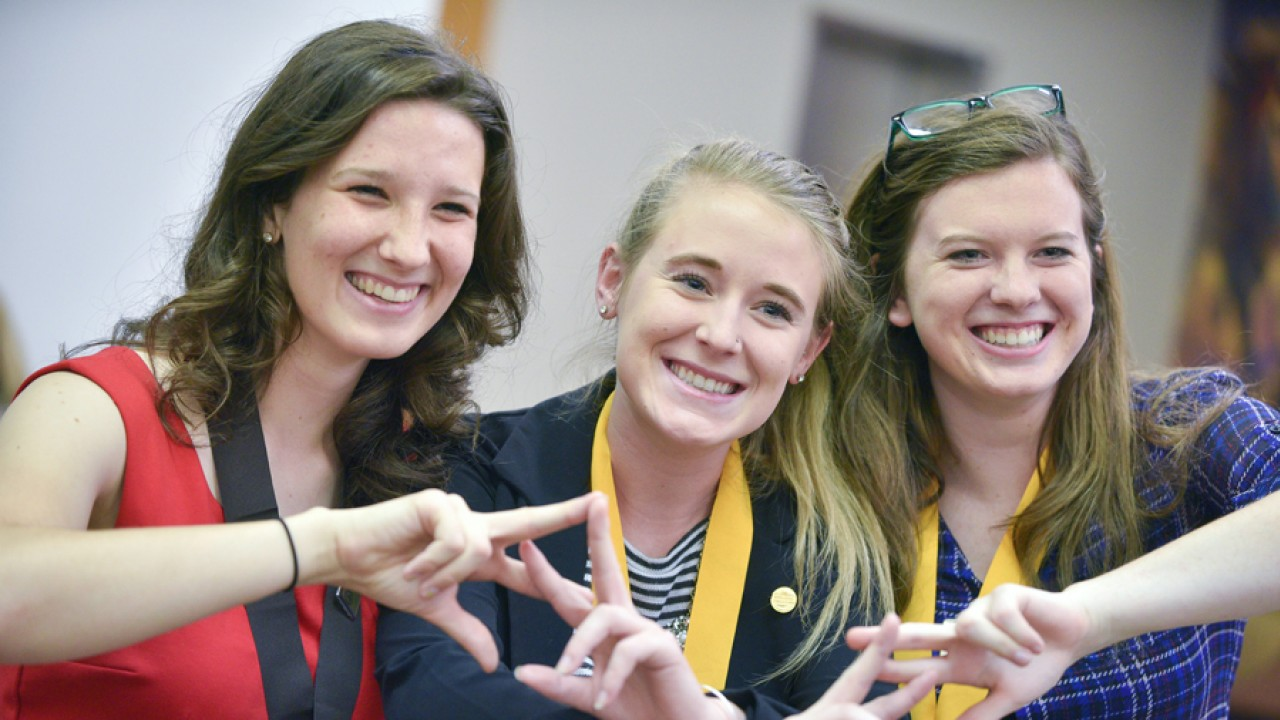 Three female honors students smiling and holding their hands up.