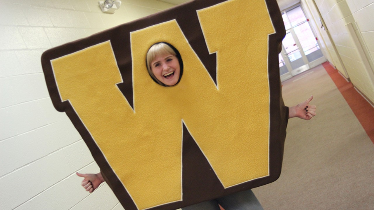 Abbie Griffith wearing the W costume giving a thumbs up to Western.
