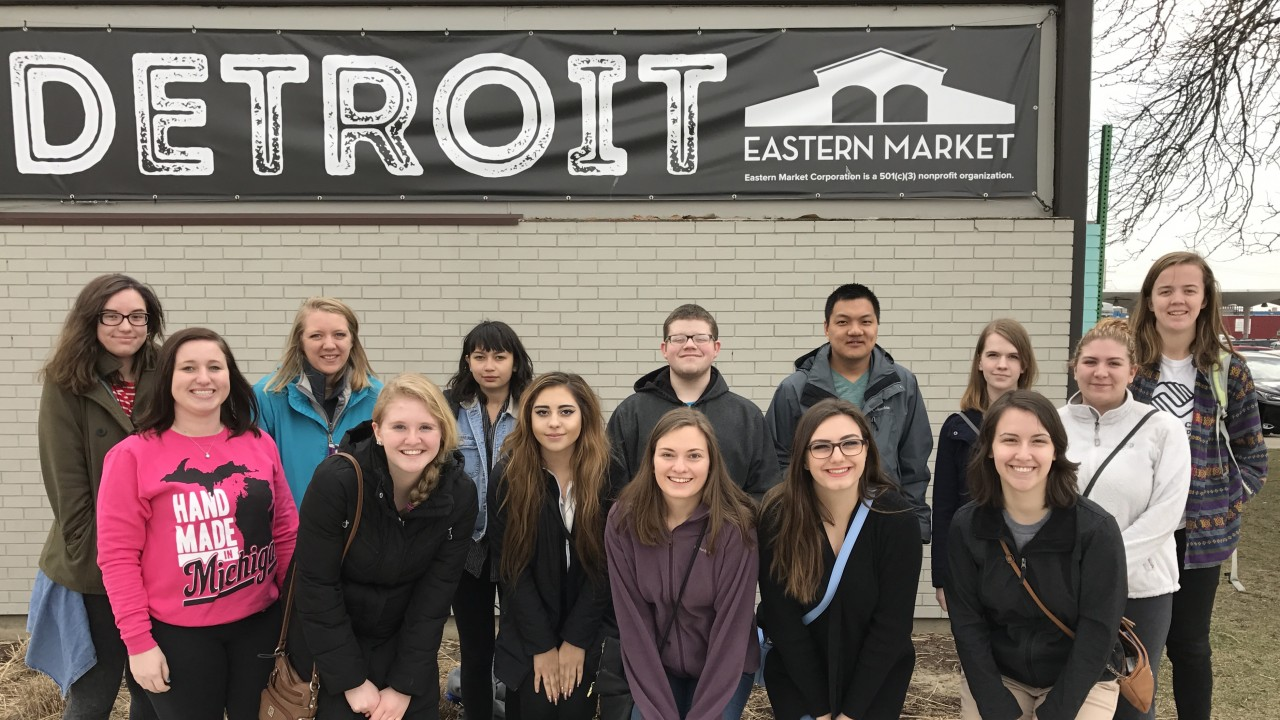 Honors Students in front of the Detroit Eastern Market Banner.