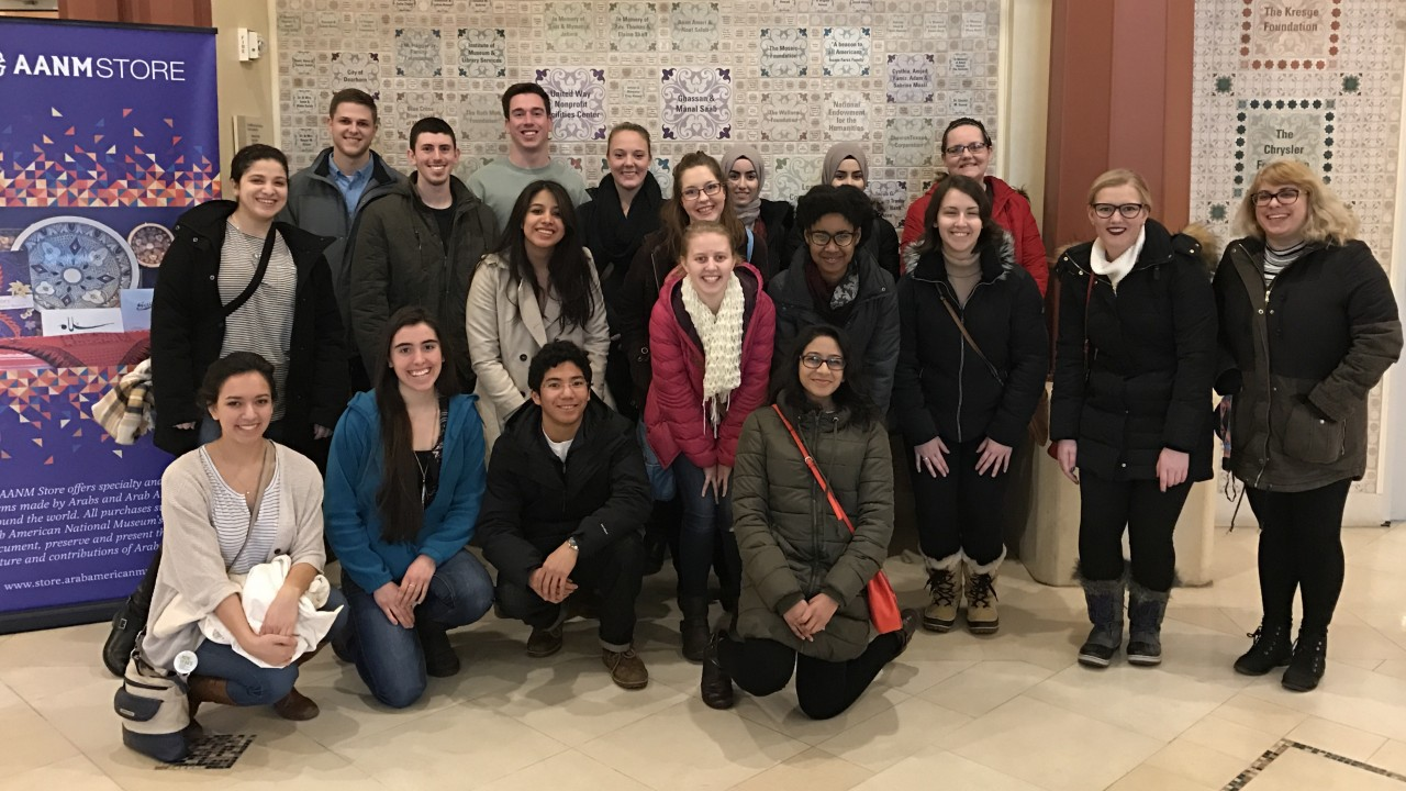 Honors students in front of a decorated wall at the Arab-American Museum.