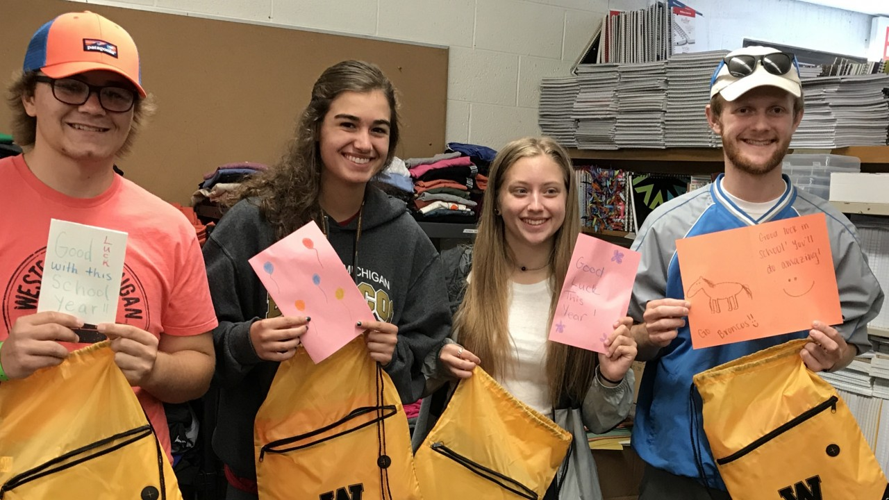 Four honors students standing in an office holding backpacks and handmade cards for elementary school students.