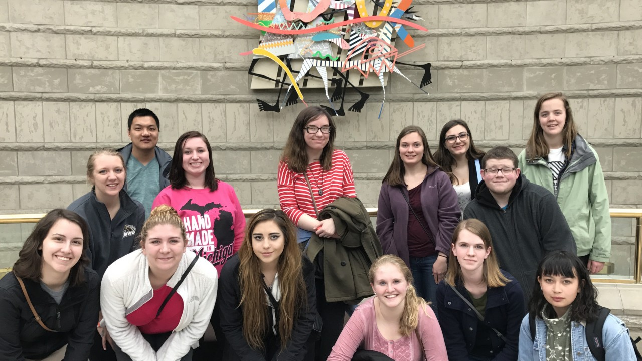 Honors students standing in front of artwork on a wall at the Charles H. Wright Museum