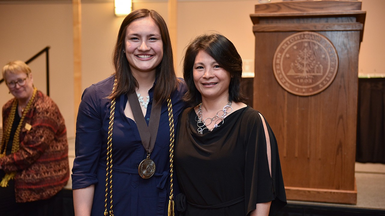 Honors college graduate Marine Bolliet with her mother standing in front of a podium at the honors college graduation ceremony.