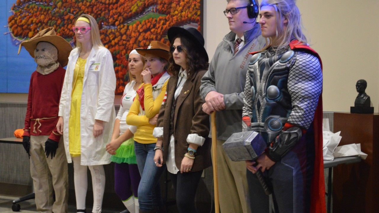 Students dressed in Halloween costumes standing in front of a painting in the honors college lounge.