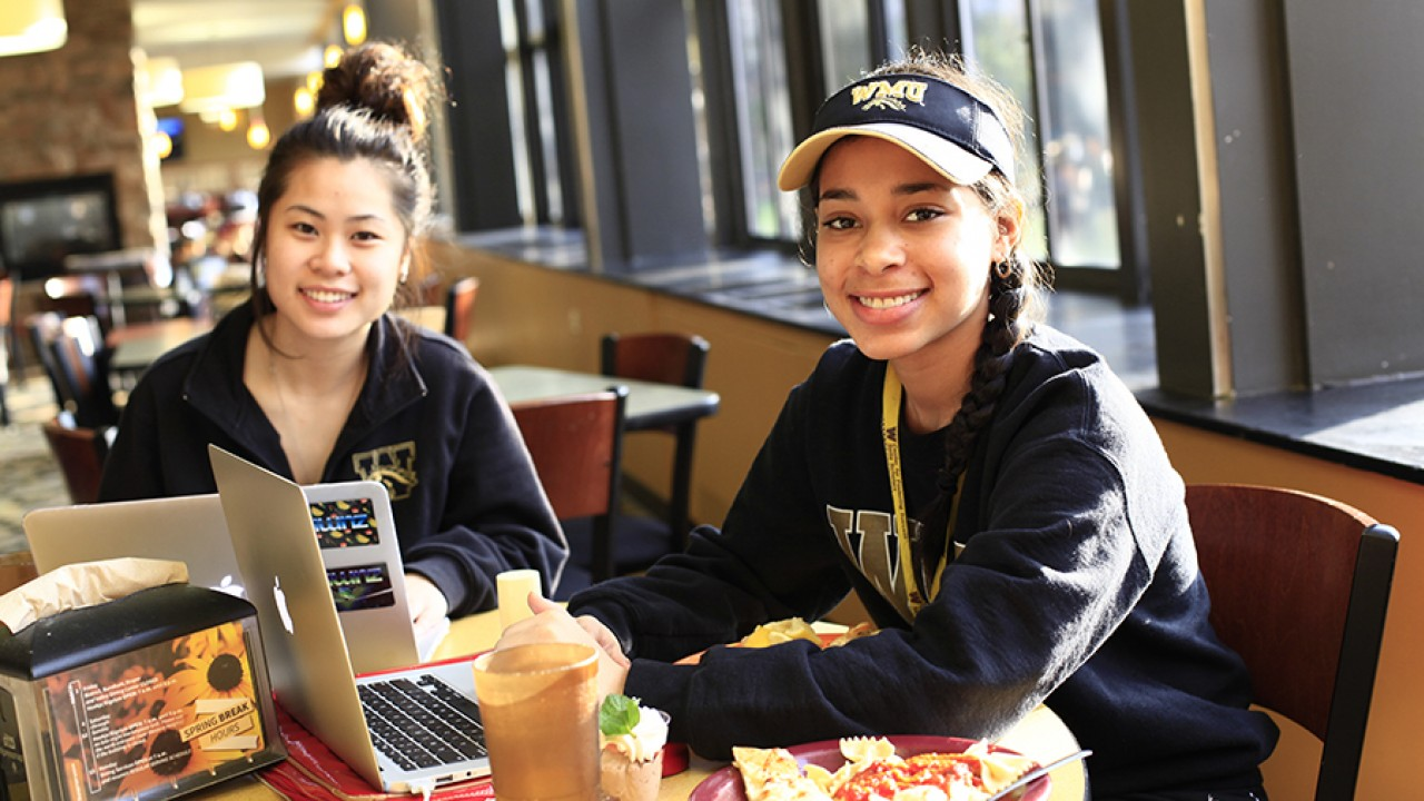 Two female students sitting at a table working on laptops and eating lunch wearing WMU gear.