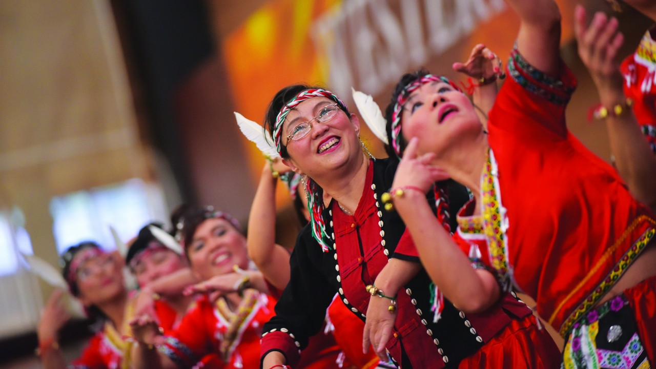Women wearing red clothing with feathers in their hair performaing a dance.