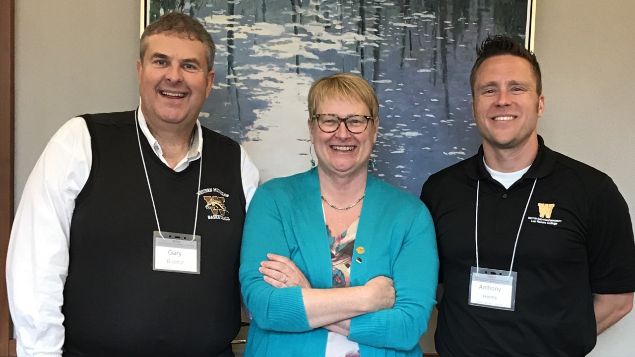 Gary H. Bischof, Jane Baas, Anthony Helms standing in front of some artwork at an honors conference in Ohio.