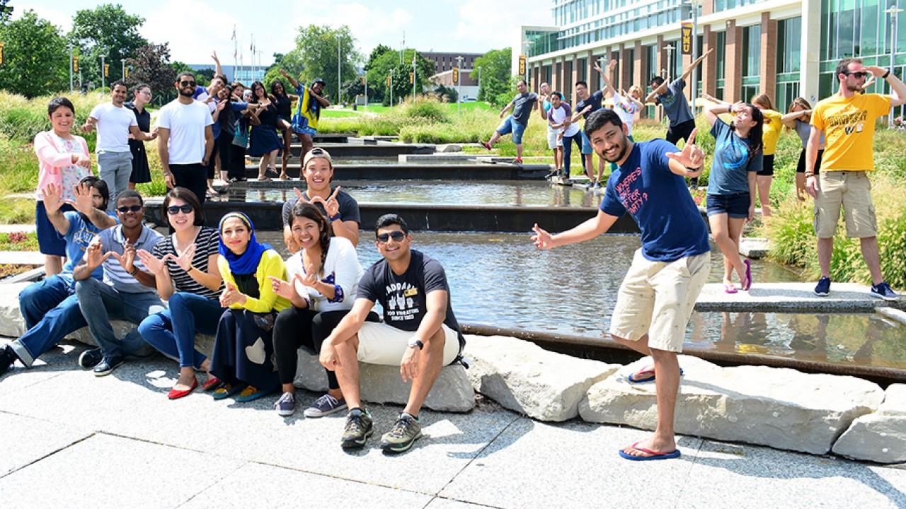 A group od students standing and sitting around the water feature in front of Sangren hall making Ws with their hands.