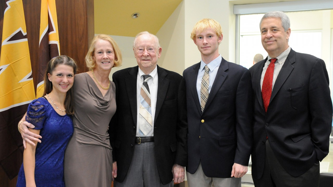 Carl Lee with his daughter, son in law, and grandchildren standing in the lounge at the reopening of the honors college.