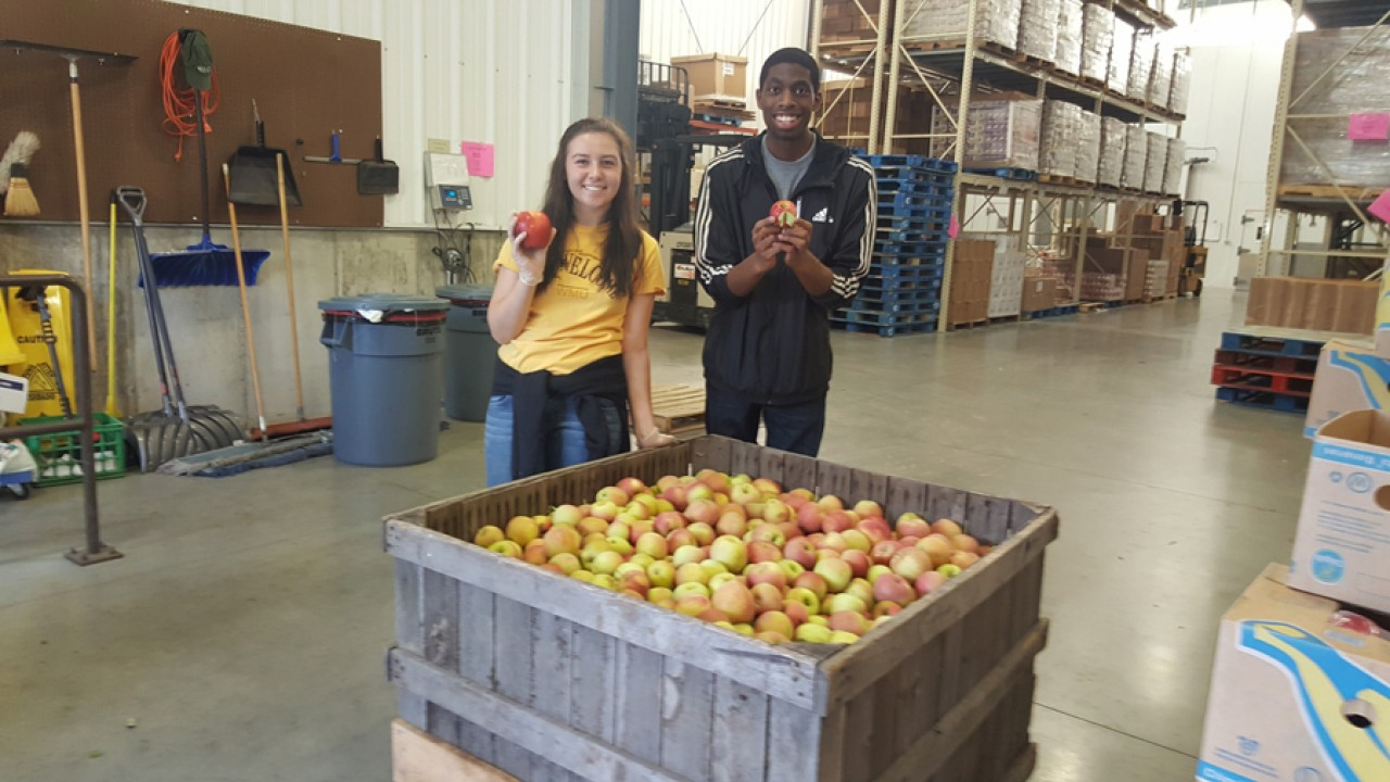 Male and female honors college students holding apples at Loaves and Fishes.