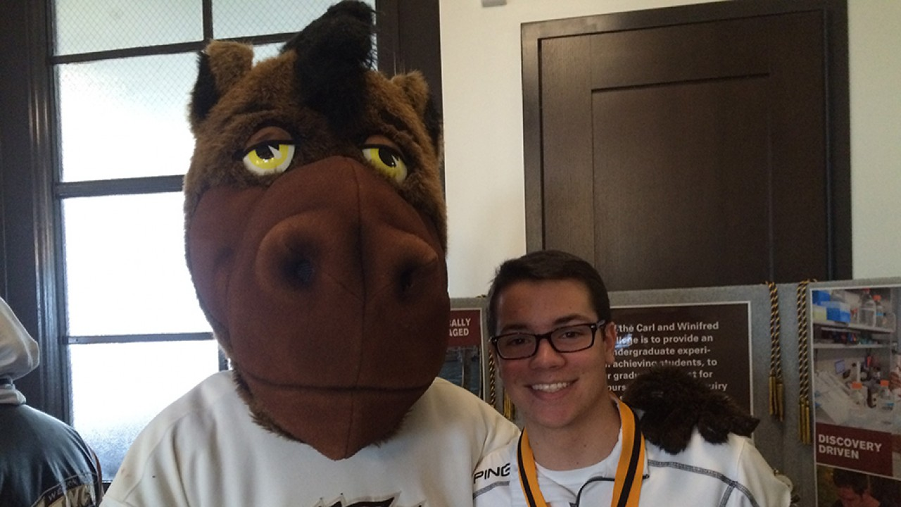 Buster Bronco and an honors college student standing in front of an informational display.