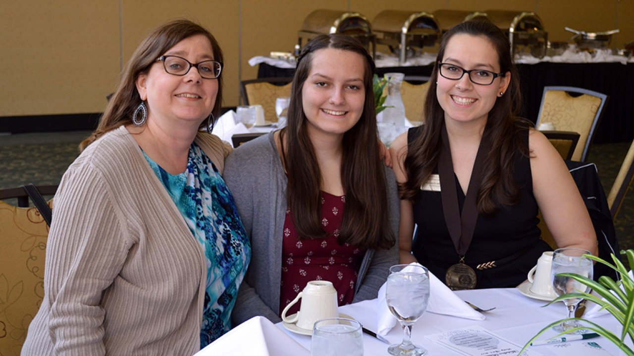 Three women seated at a table attending the annual Medallion brunch.