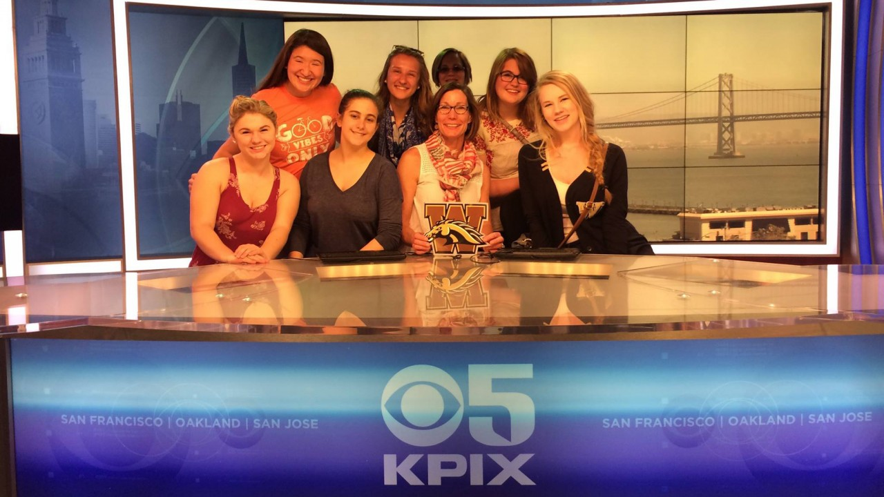 A group of students holding a W sitting at a news anchor desk at KPIX television station in San Francisco.