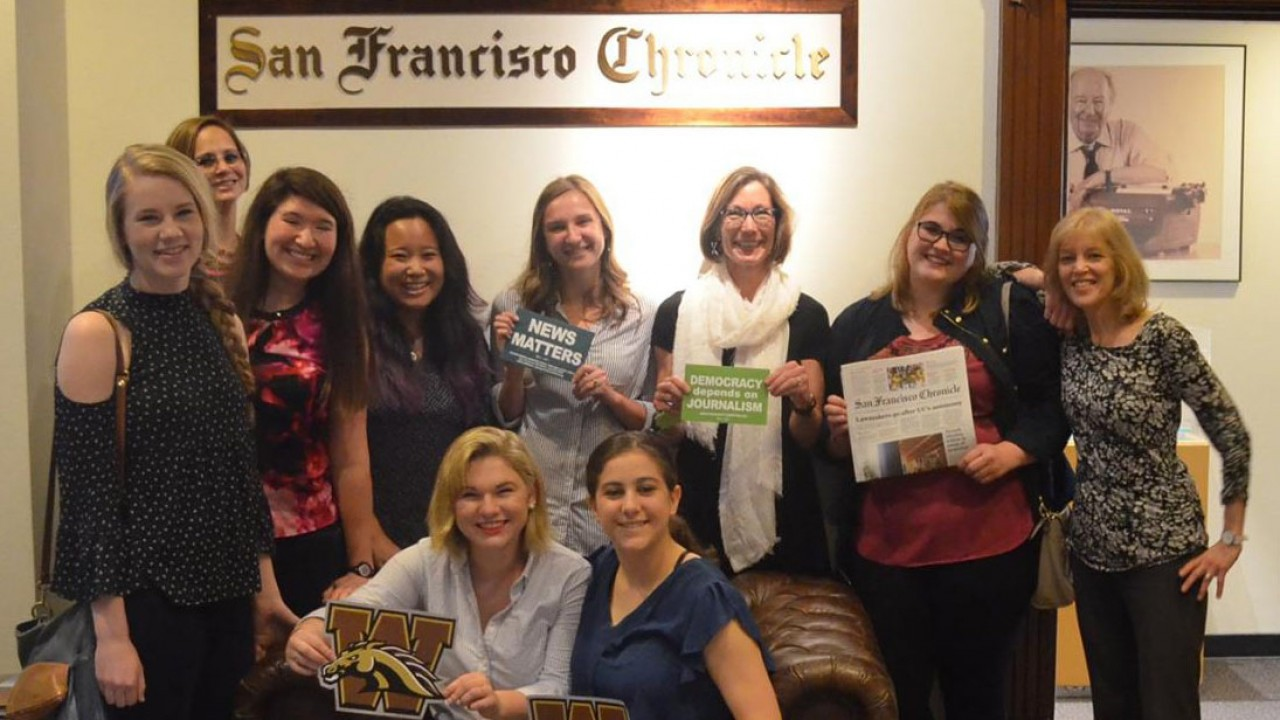 Students holding a W and a newspaper standing in front of the San Francisco Chronicle sign.