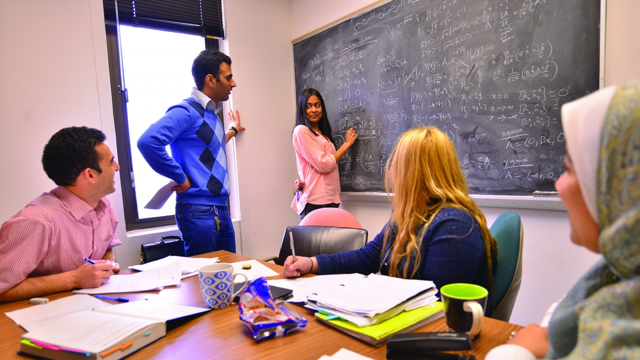 Three students sitting at a table, one student standing at a window and one student working at a chalkboard.