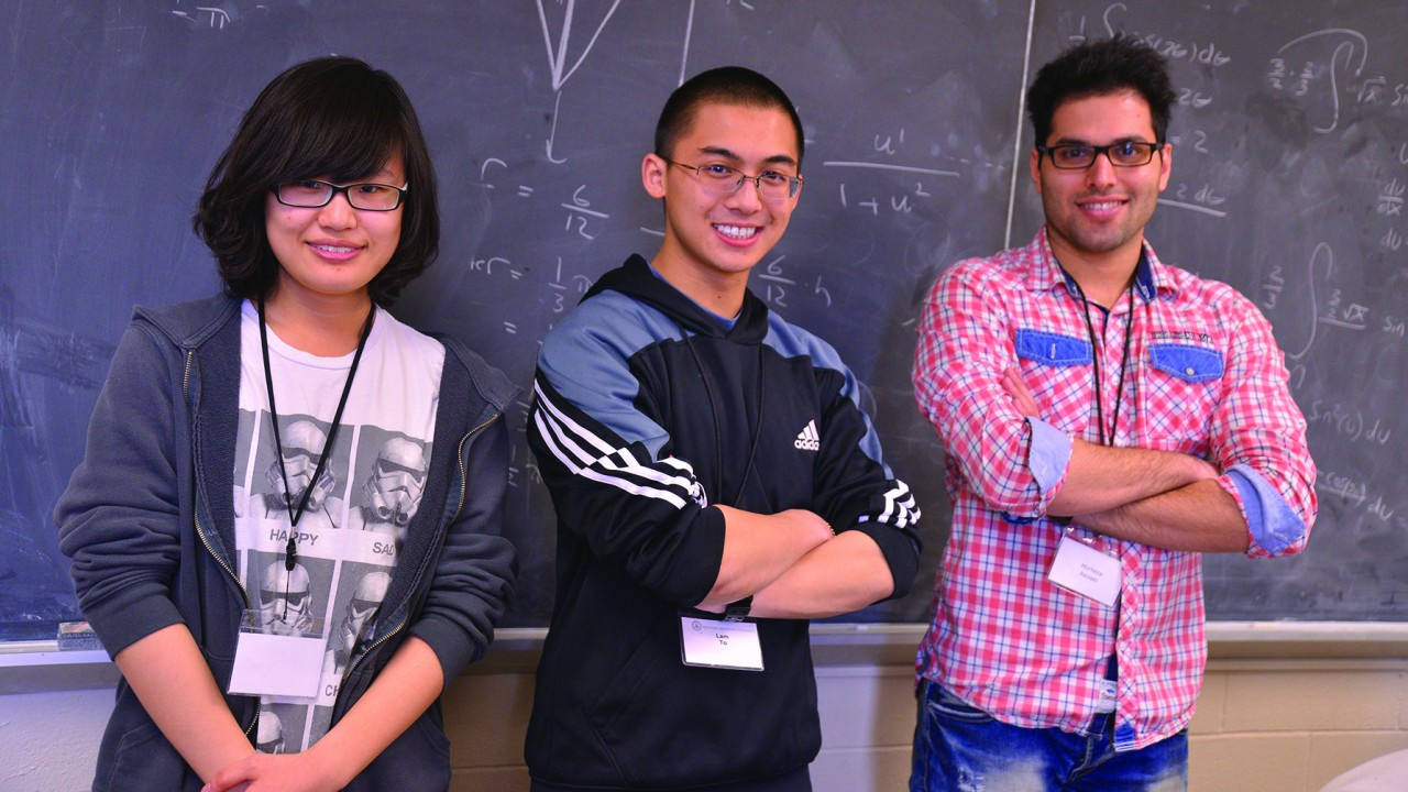 Three students standing in front of a chalkboard.