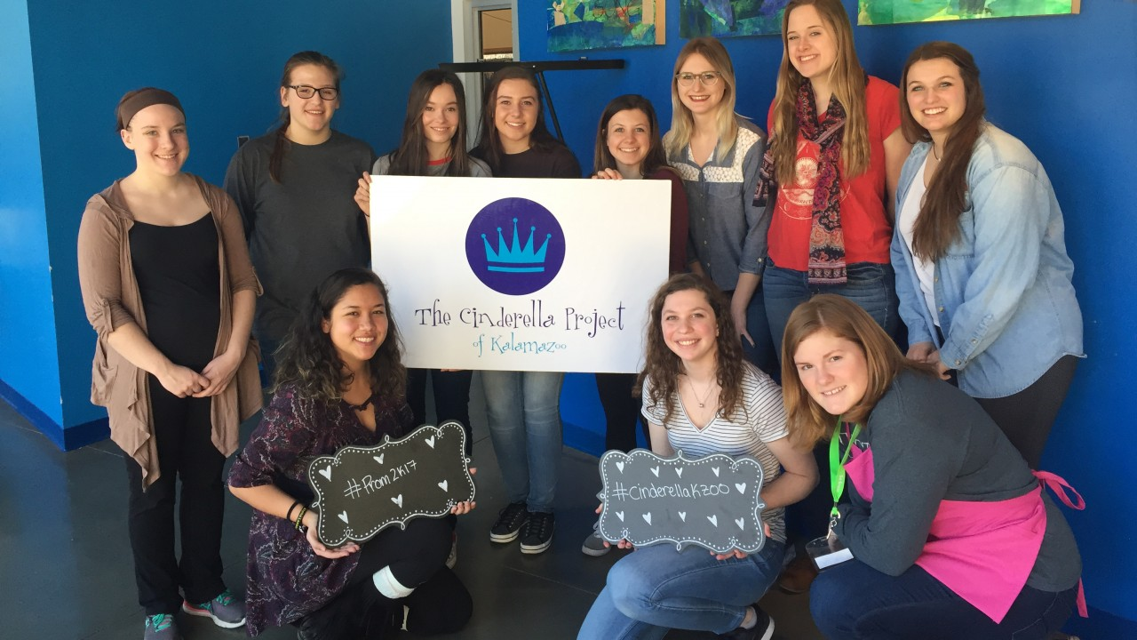 A group of honors college students holding a Cinderella Project sign in front of a blue wall.