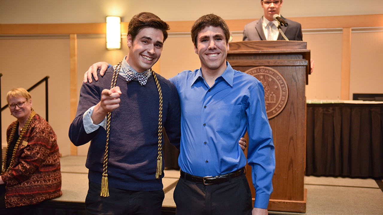 An honors college graduate and his corder standing in front of a podium at the honors college graduation ceremony.