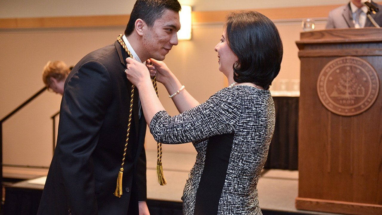 An honors college student receiving his honors cords in front of a podium at the honors college graduation ceremony.
