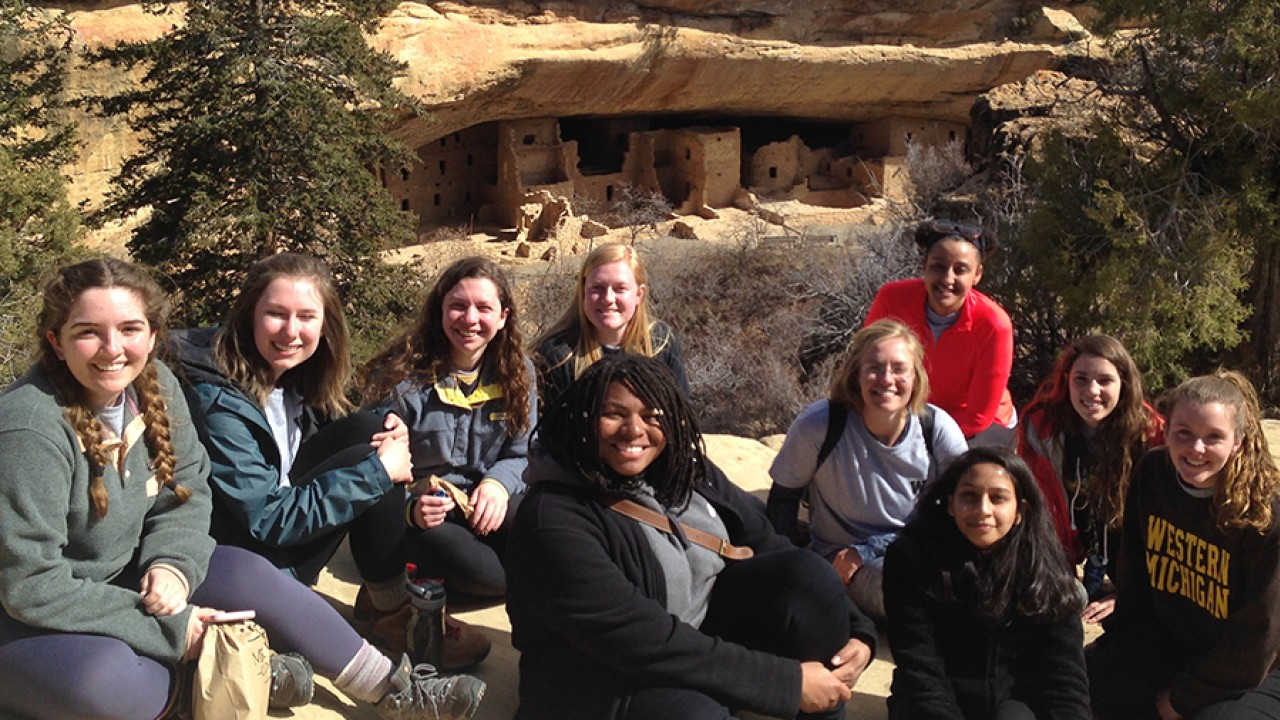 Honors students seated with Anasazi dwellings in the cliffside behind them.