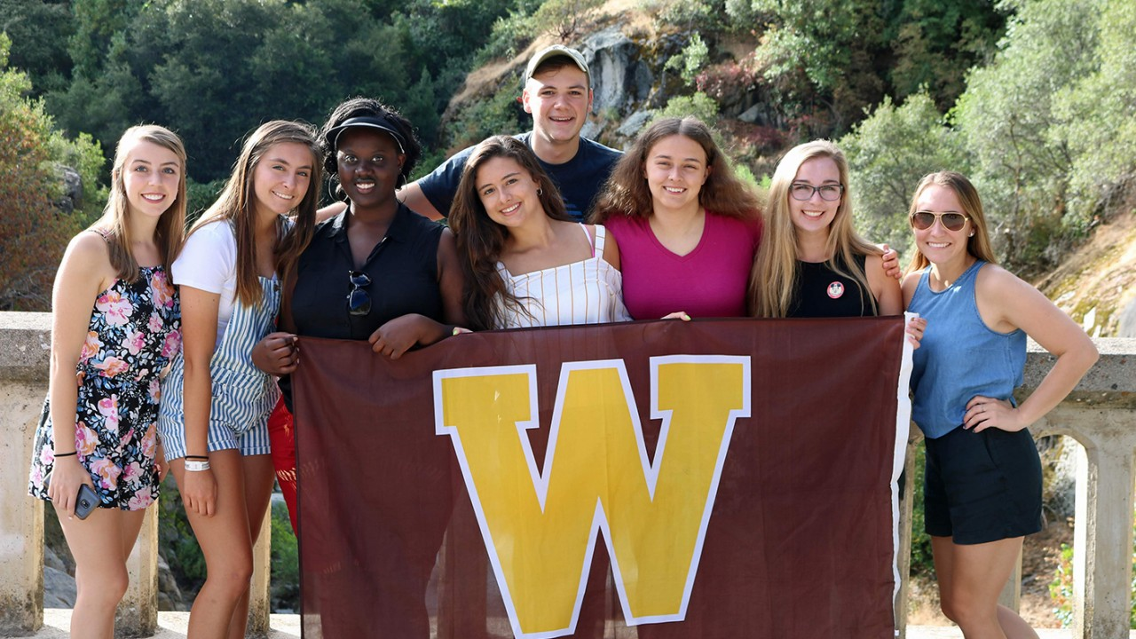 Students holding a W flag in front of a waterfall.