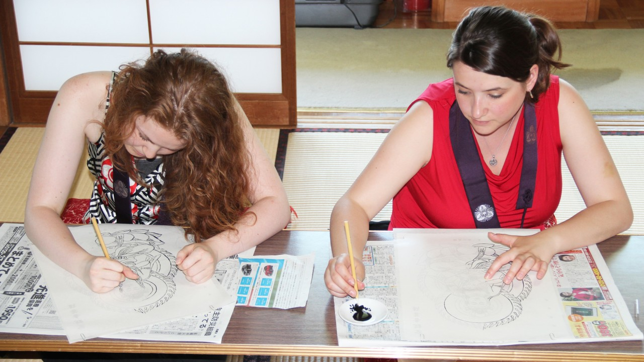 Two American students trace Chinese drawing while sitting on the floor during their study abroad trip