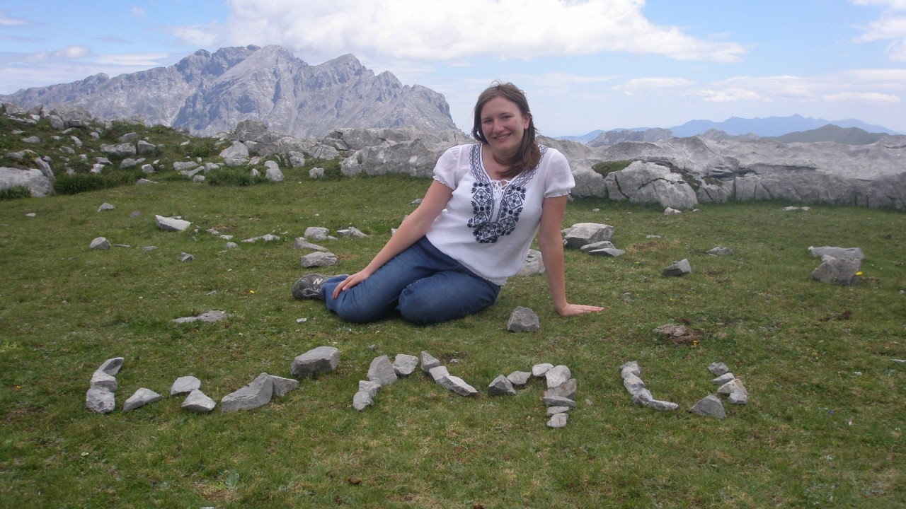 Krystalle Double writes WMU with rocks while sitting in front of a mountain range while studying abroad