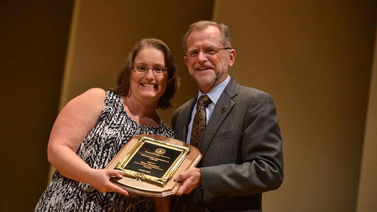 Terri Riemland receiving the Make a Difference Annual Award from President Dunn