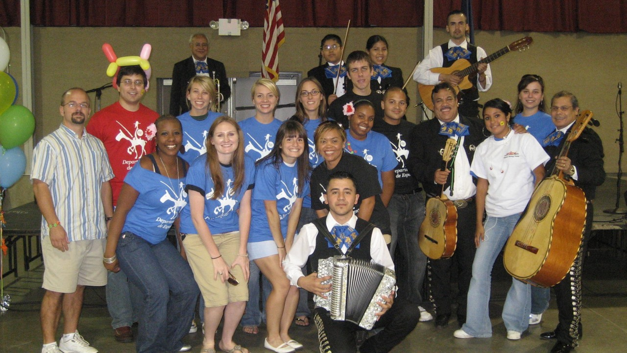 Dr. Millar with a group of students, some of whom are holding various musical instruments
