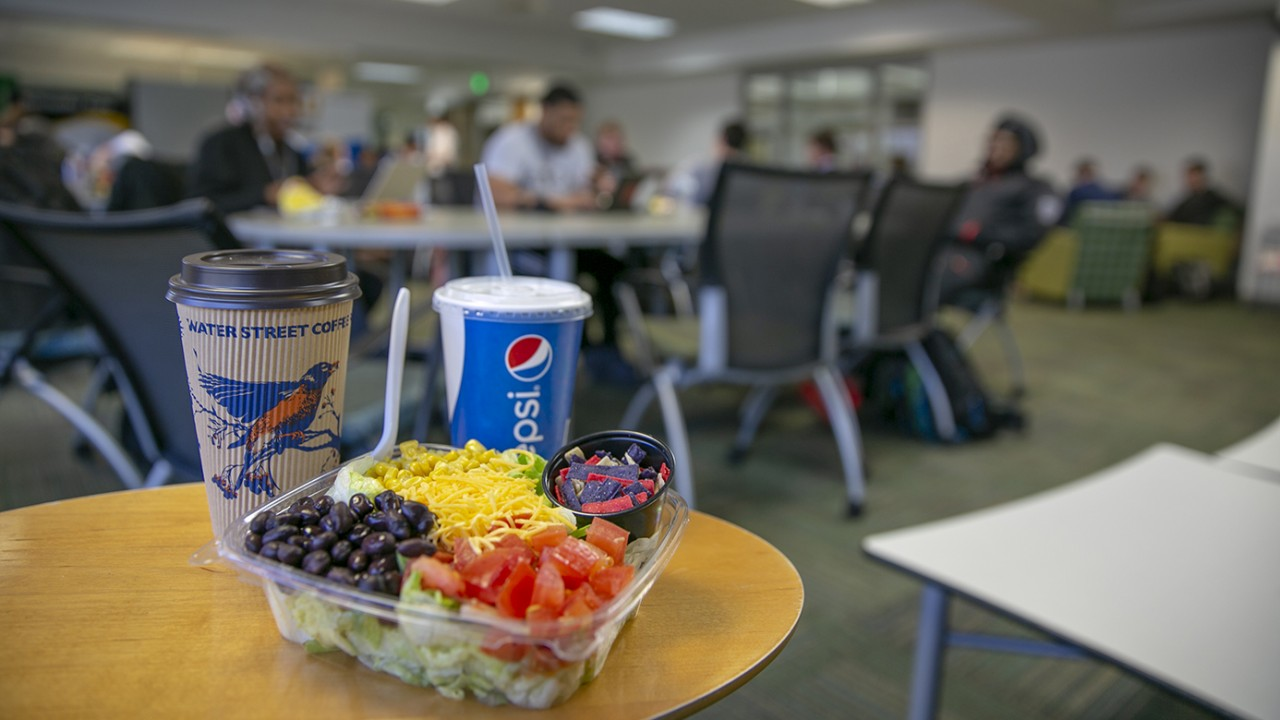 Salad, coffee and soda on desktop in seating area of Schneider Cafe