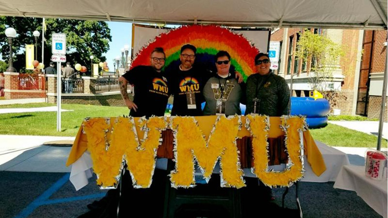 Members of Pride Alumni Network pose behind the Homecoming 2016 table.