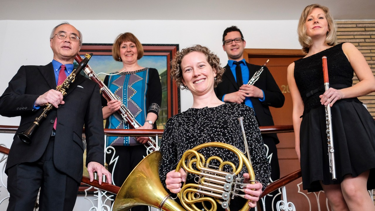 posed photo of the Western Wind Quintet with horn player surrounded by clarinetist, bassoonist, oboist and flutists.