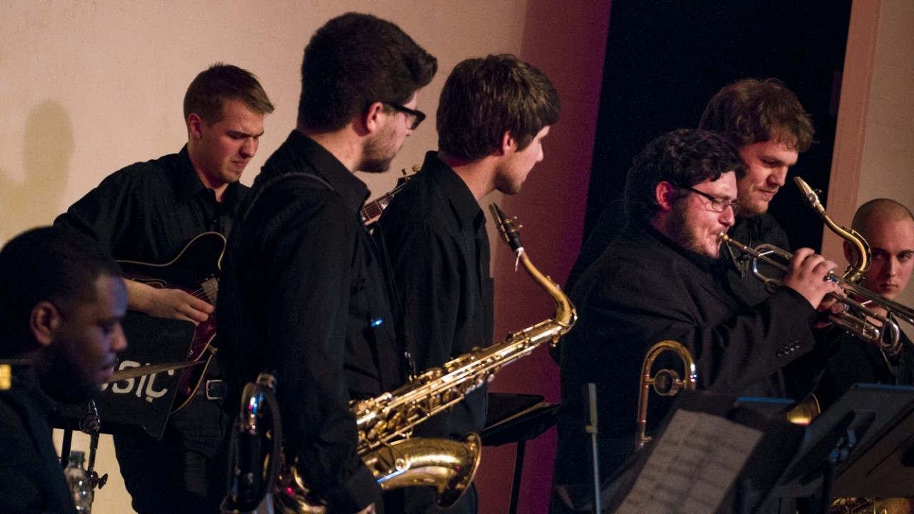 close up image of a jazz ensmeble with a saxophonist, guitarist, trumpet player and trombonist