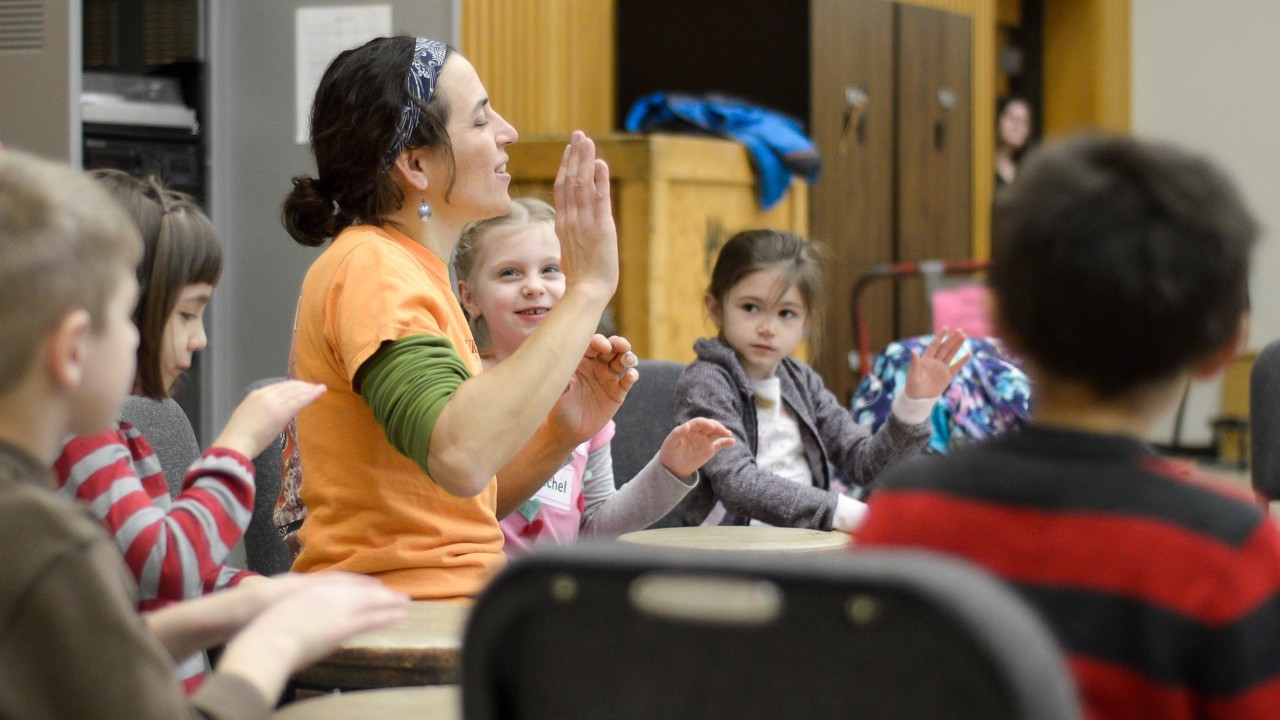 female drum instructor teaching a group of small children