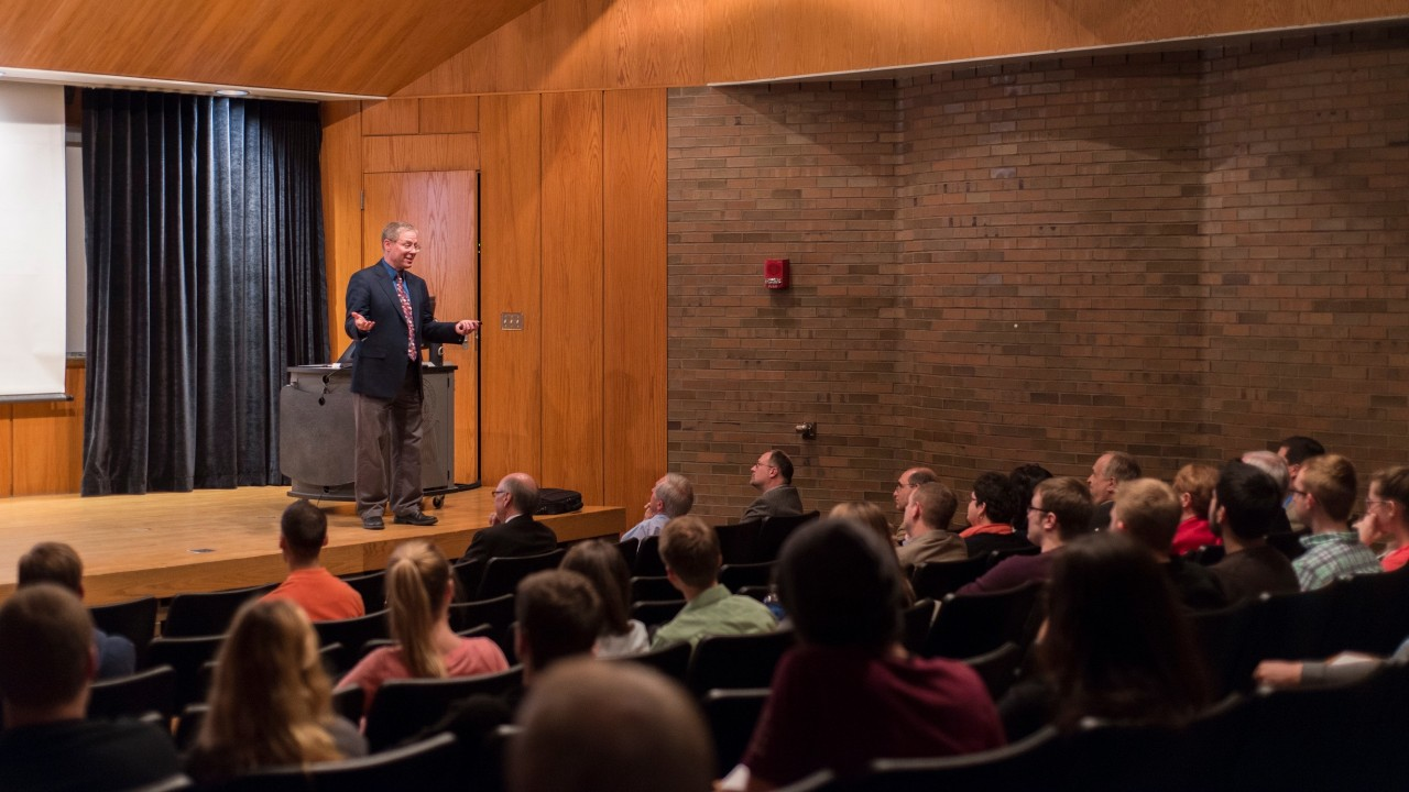 a man lecturing on a stage to a full audience in a lecture hall
