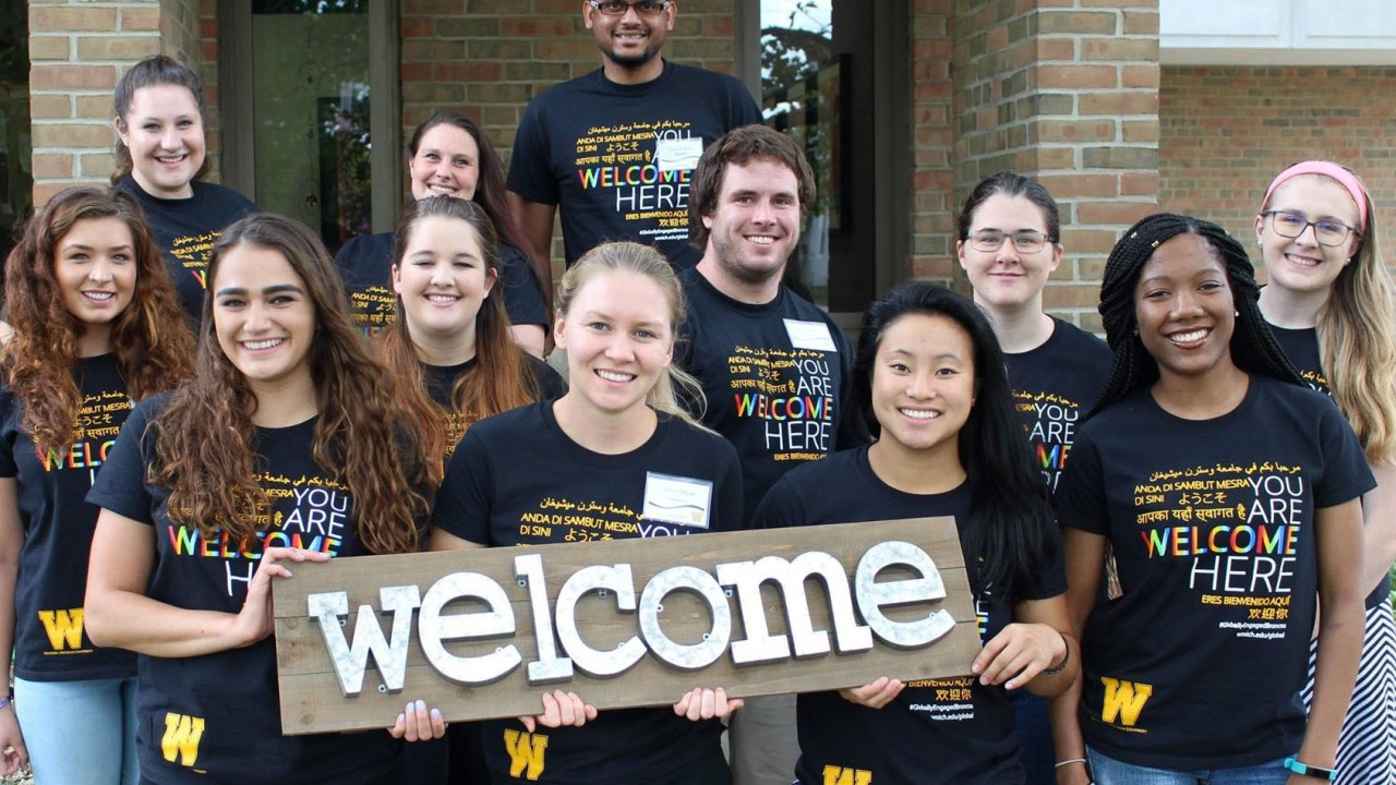 10 DSS student peer mentors smiling and holding a sign that says Welcome