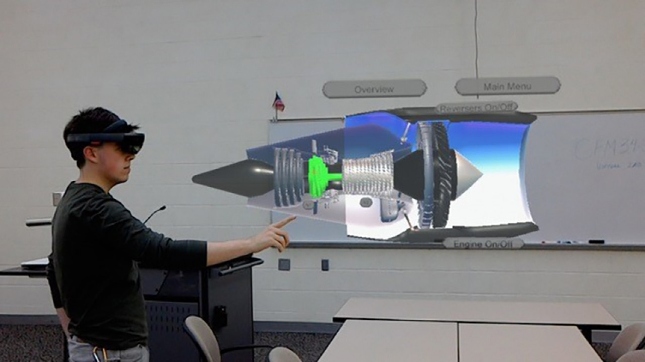 Photo of a Western Michigan University College of Aviation student uses Microsoft's HoloLens mixed reality technology to interact with a virtual jet engine.