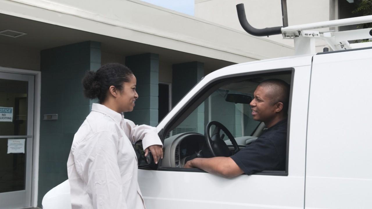 Photo of workers talking near service van.