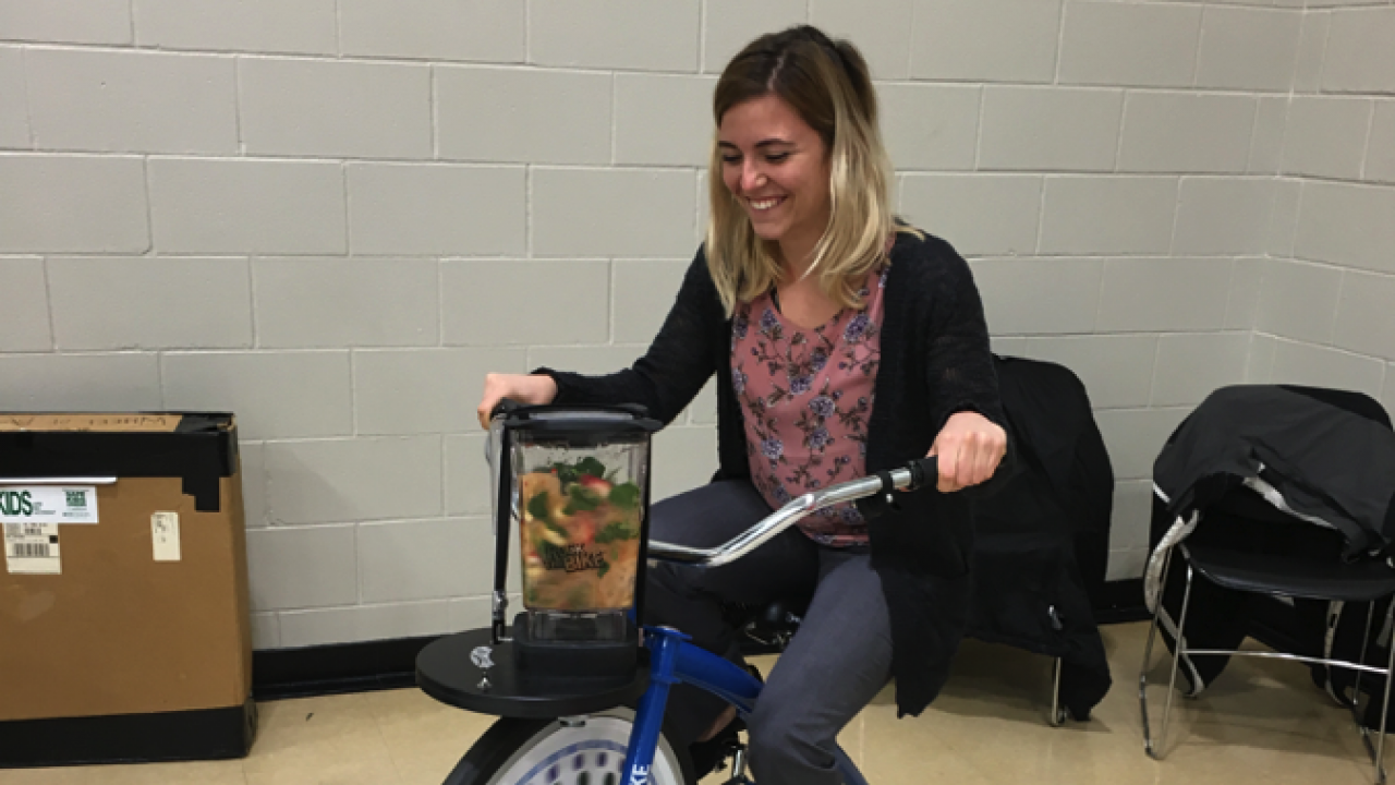 Student riding an electronic bike that is preparing a smoothie