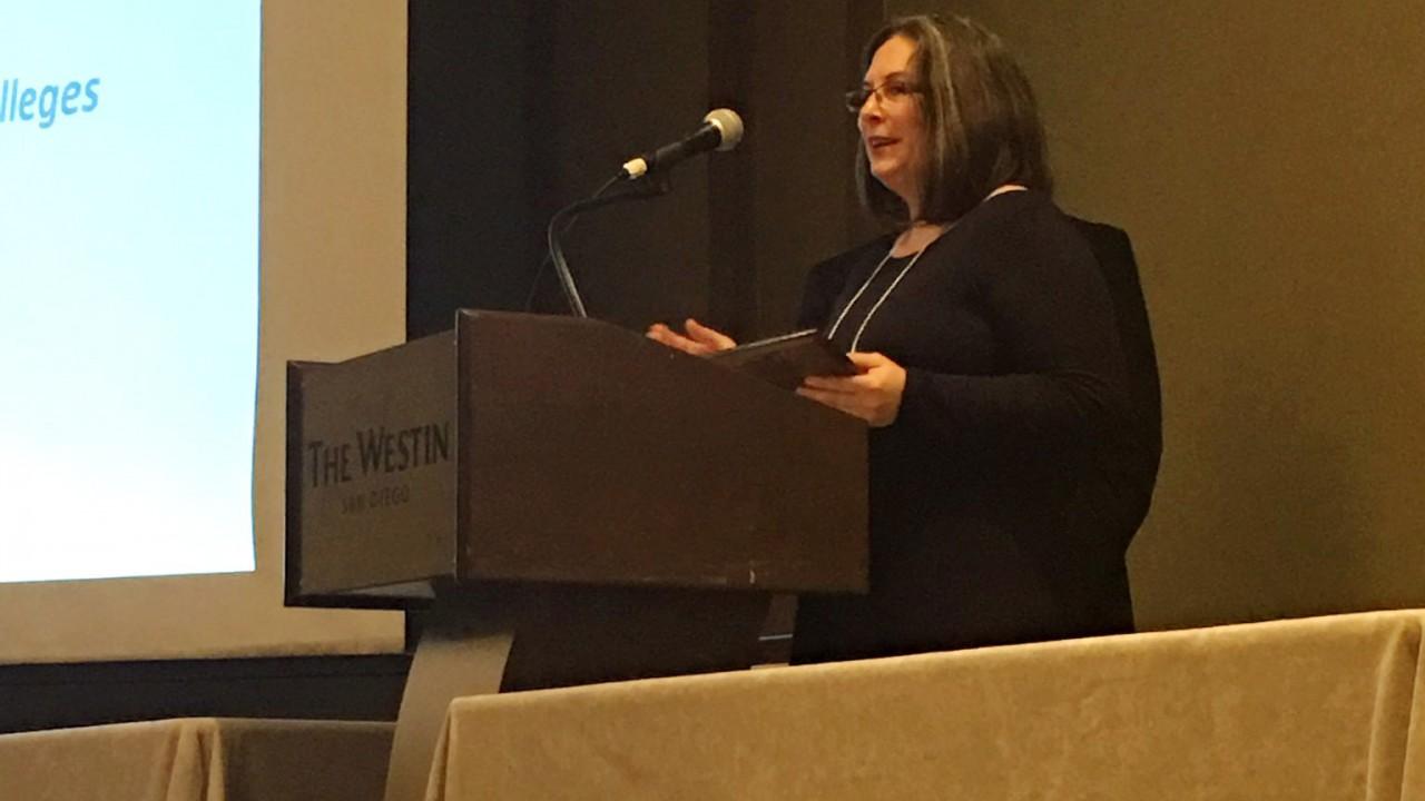 Dr. Regina Garza Mitchell at podium.