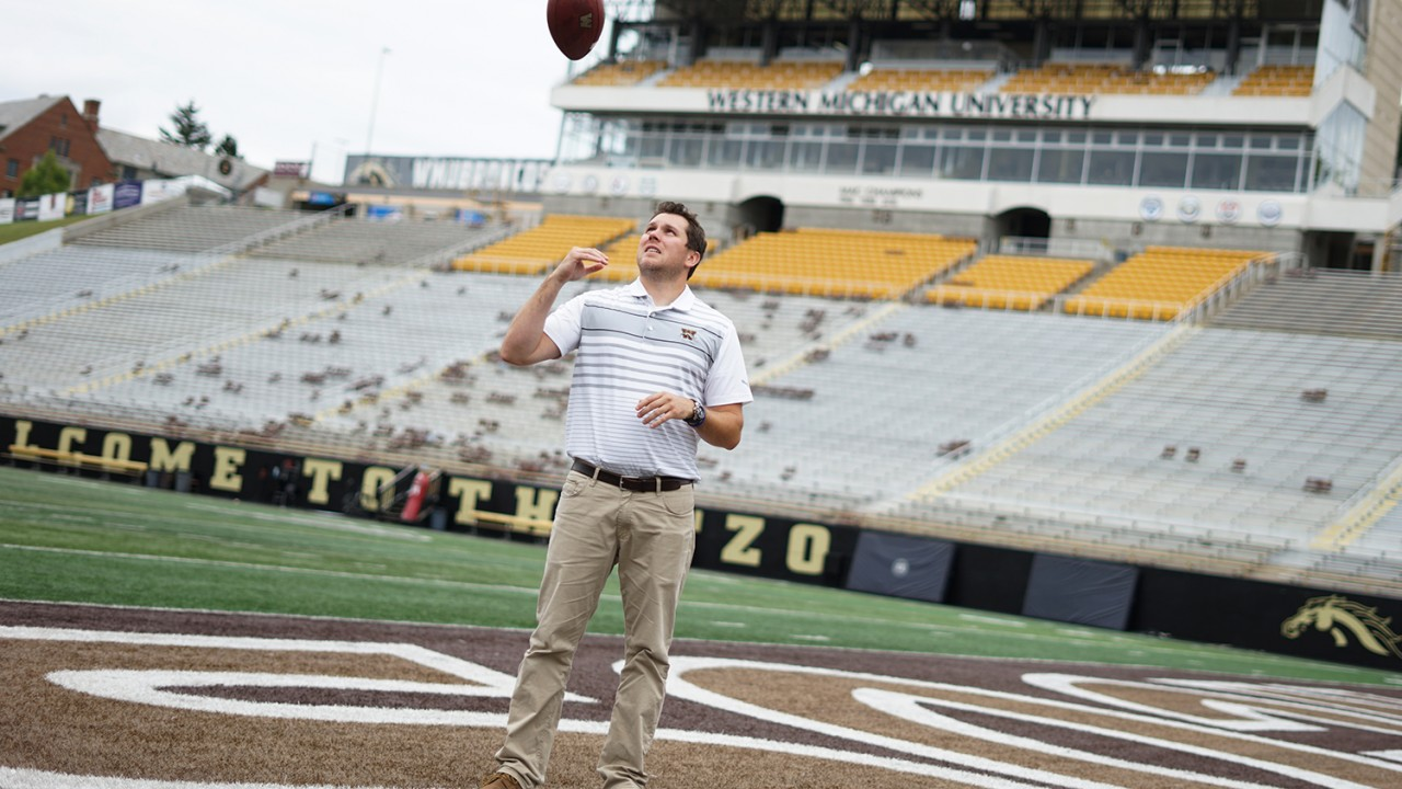 Thomas tossing a football in the air at Waldo Stadium