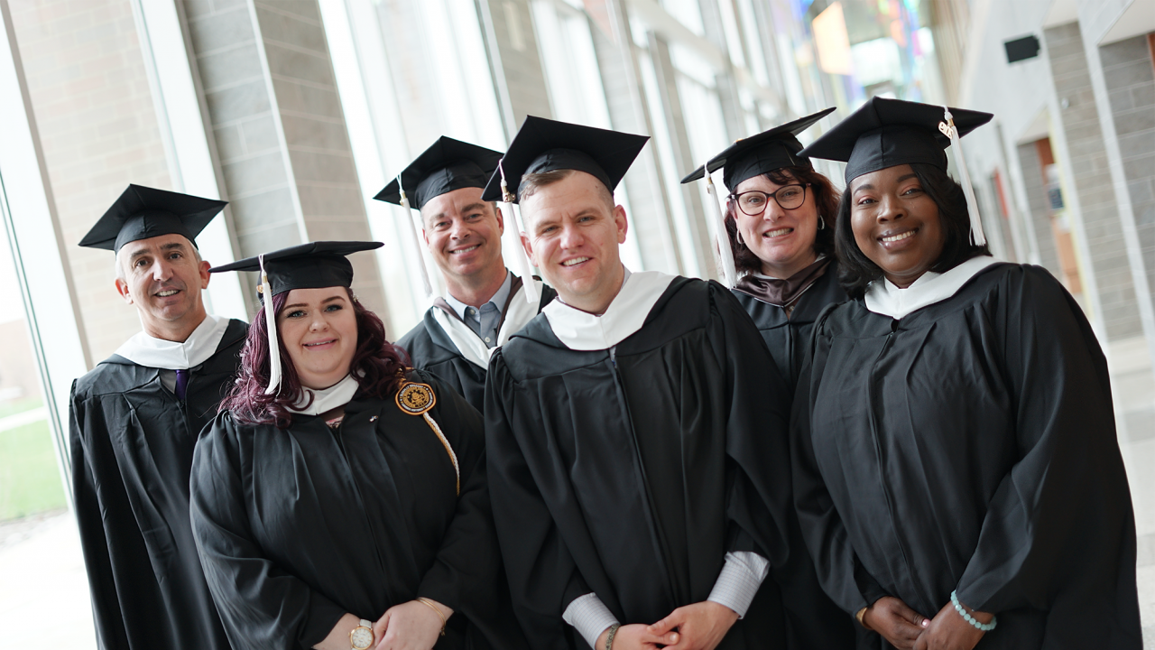 6 graduates in cap and gown in sangren hall